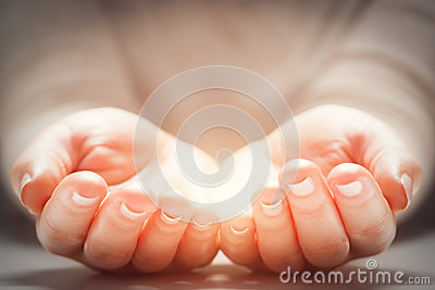 Light in woman's hands. Concepts of sharing, giving, new life