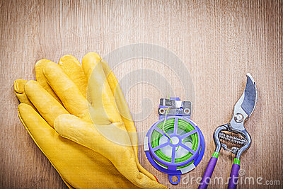 Pair of safety gloves sharp secateurs soft wire tie on wooden bo