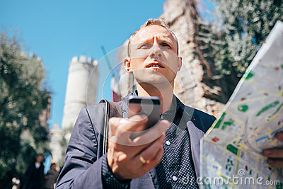 Tourist man try navigate himself with map and smartphone in unkn