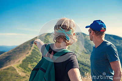 Two travelers discuss about itinerary on the top of mountain hil