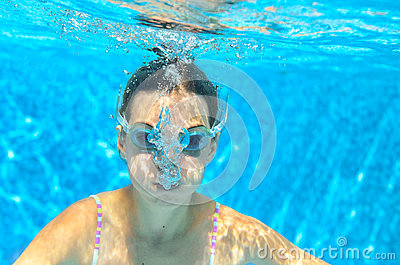 Child swims in pool underwater, funny happy girl in goggles has fun under water and makes bubbles, kid sport