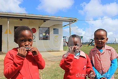 Group of African children playing harmonica outdoors in a playground, Swaziland, southern Africa