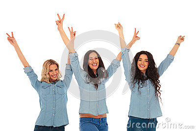 Three excited young casual women with hands in the air