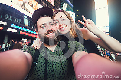 Happy dating couple in love taking selfie photo on Times Square in New York while travel in USA on honeymoon