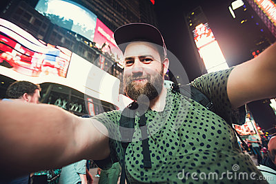 Funny bearded man backpacker smiling and taking selfie photo on Times Square in New York while travel across USA
