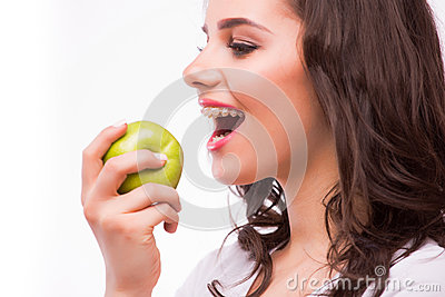 Young girl with brances eat apple. Female teeth with dental braces and apple.