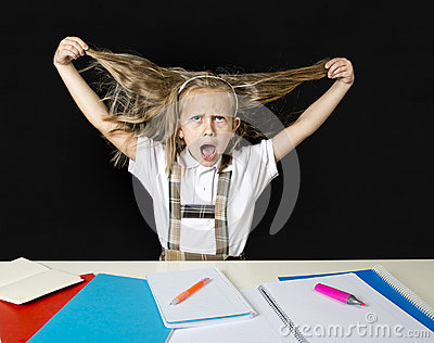 Crazy junior schoolgirl sitting on desk in stress working doing homework pulling her blond hair crazy