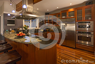 Contemporary upscale home kitchen interior with wood cabinets and floors, granite countertop and stainless steel appliances