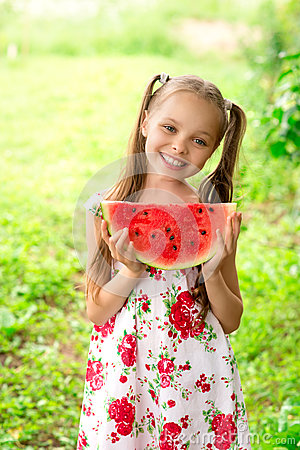 Smiling little girl with blue eyes eats a slice of watermelon