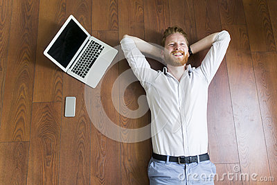 Man laying on the floor by the laptop