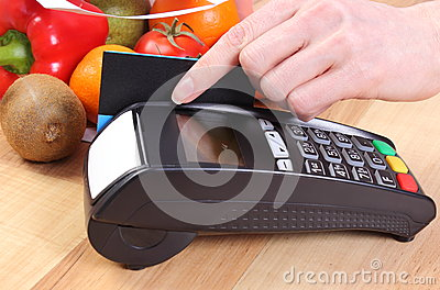 Payment terminal with credit card, fruits and vegetables, cashless paying for shopping