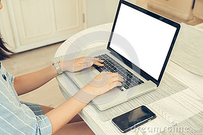 Female person sitting front open laptop computer and smart phone with blank empty screen for your information or content.