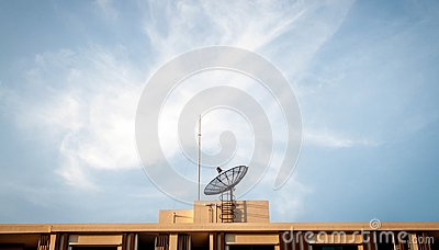 Satellite dish on building roof with sky background