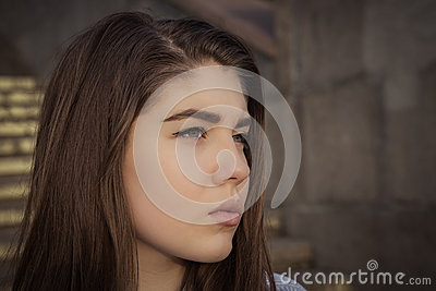 Outdoor close up portrait in profile of a pretty teenage girl