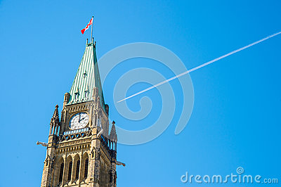 Canadian Parliament Peace tower in Ottawa, with a plane over the
