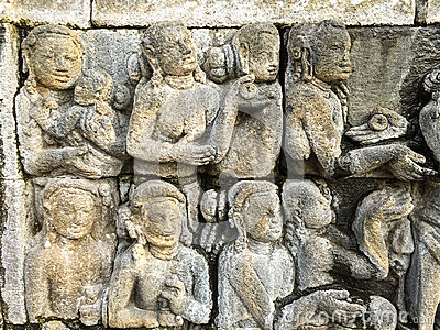 Engraved figures depicts the story of Buddha on a stone wall of Borobudur, Indonesia