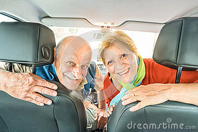 Happy senior retired couple ready for driving car on road trip