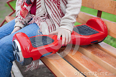 Girl holding modern red electric mini segway or hover board scooter