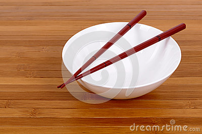 White empty rice bowl wooden chopsticks bamboo background