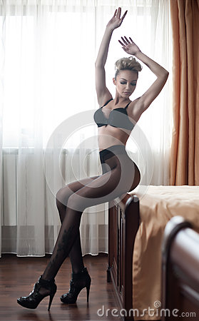 Beautiful sexy blonde young woman wearing black lingerie, bra and tights, sitting on bed. Fashionable female with attractive body