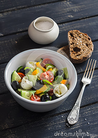 Fresh salad with tomatoes, cucumbers, peppers, olives, cheese  in a ceramic bowl and rye bread ciabatta