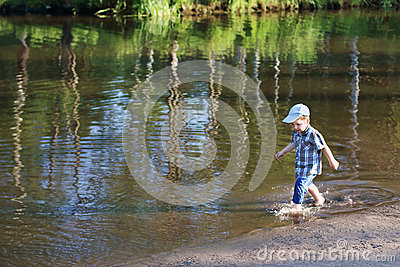 Little happy boy smiles and goes in water of pond