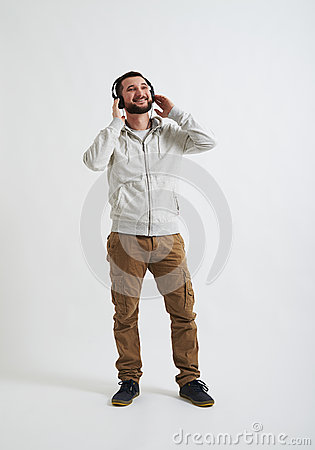 Man in casual wear is listening to music
