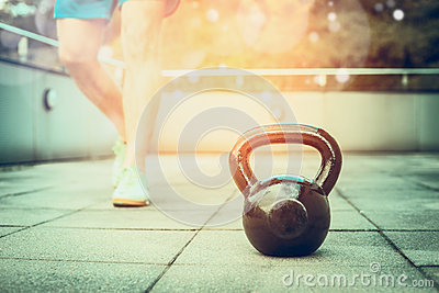 Training process with the kettlebell in the fresh air,  young man trains nature background