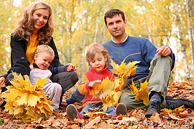 Family of four with yellow maple leaves in wood