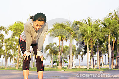 Tired female runner took a break after hard workout outdoors