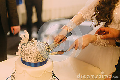 Beauty bride and handsome groom are cutting white wedding cake decorated with blue riband