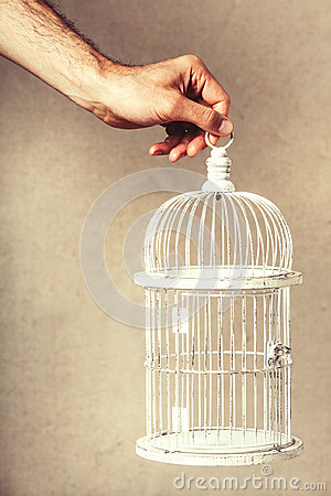 Hand holding an empty cage. Absence of ideas and dreams. Freedom and hope.