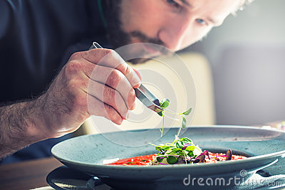 Chef in hotel or restaurant kitchen cooking, only hands. He is working on the micro herb decoration. Preparing tomato soup