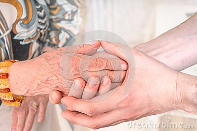 Man holds hands of eldery woman. Senior help concept