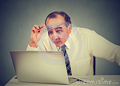 Shocked man reading message on computer in office