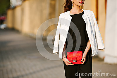 Young stylish woman goes in the city with a red trendy bag. On the shoulder of the girl bag, dressed in a black Trouser