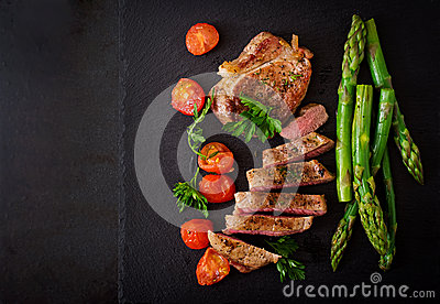 Juicy steak medium rare beef with spices and tomatoes, asparagus.