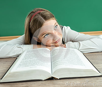 Fantasy pupil looking up as if daydreaming or thinking of something pleasant while sitting at the desk with open book.