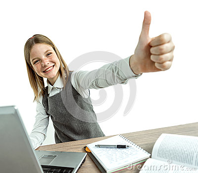 Happy smiling young girl showing thumbs up gesture while using her laptop computer.