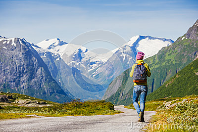 Young hipster female traveler on road
