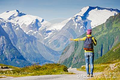Travel hitchhiker woman walking on road during holiday travel