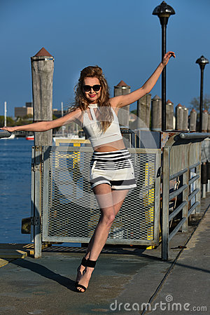 Fashion model posing pretty on the pier in sunny weather wearing white top, sailor shorts and sunglasses.