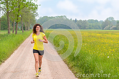 Smiling healthy young woman jogging in nature
