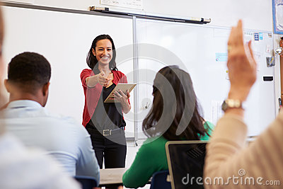 Teacher with tablet and students at an adult education class