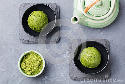Green tea matcha ice cream scoop in bowl on a grey stone background Top view