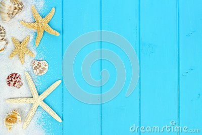 Side border of sand, seashells and starfish on blue wood