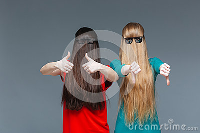 Two comical women with faces covered by long hair gesturing