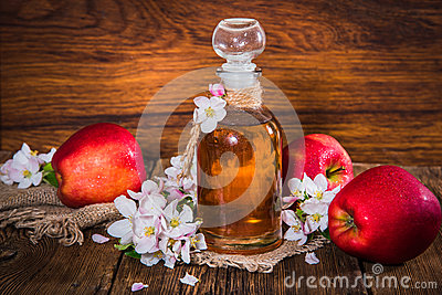 A bottle of apple cider vinegar (cider), fresh apples and apple-tree flowers on a wooden background.