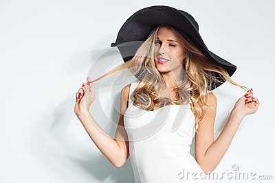 Beautiful blonde woman in black hat and white elegant evening dress posing on isolated background.Fashion look.Stylish