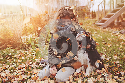 Happy child girl playing in autumn with her cavalier king charles spaniel dog